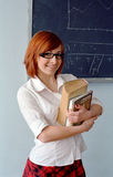 Redhead schoolgirl in front of blackboard Stock Photo
