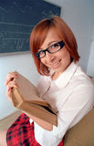 Redhead schoolgirl reading book Royalty Free Stock Photo