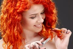Redhead with scissors. Picture of lovely redhead with scissors over grey royalty free stock image