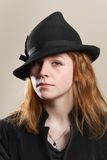 Redhead serious in black hat and jacket Royalty Free Stock Images