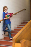Redhead serious student reading notes on the stairs Stock Photos