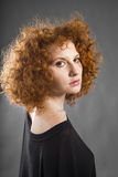 Redhead curly young woman. Portrait in studio closeup royalty free stock photography