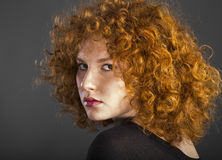 Redhead curly young woman. Portrait in studio closeup stock photo