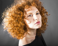 Redhead curly young woman. Portrait in studio closeup royalty free stock photo