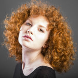 Redhead curly young woman. Portrait in studio closeup stock photography