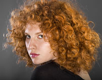 Redhead curly young woman. Portrait in studio closeup stock image