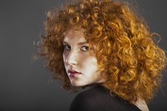 Redhead curly young woman. Portrait in studio closeup royalty free stock images