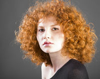 Redhead curly young woman. Portrait in studio closeup stock images