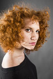 Redhead curly young woman. Portrait in studio closeup stock photos