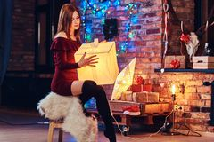 Full body redhead female. Redhead lady posing in a room with loft interior and Christmas decoration stock photography