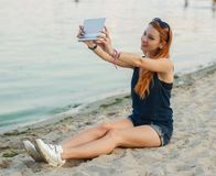 Redhead woman with tablet computer. Redhead woman with tablet computer on a beach royalty free stock photo