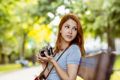 Redhead sitting on bench using her camera Stock Images
