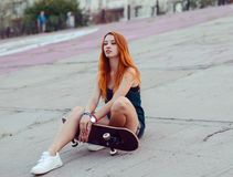 Redhead skater girl posing in skate park. Stock Photos