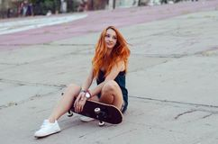 Redhead skater girl posing in skate park. Royalty Free Stock Photography