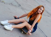 Perfect redhead girl sitting on skate board. Stock Image