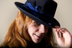 Redhead smiling in black hat touching brim. Redhead smiling in a black hat touching brim royalty free stock image