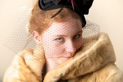Redhead smiling shyly in black veiled hat and fur coat Royalty Free Stock Photography