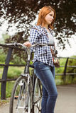 Redhead standing next to her bike Stock Photos