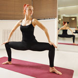 Redhead in standing yoga pose Stock Images