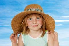 Redhead in straw hat. Cheerful redhead little girl in big straw hat Stock Photos