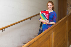 Redhead student holding folders on the stairs smiling at camera Stock Image