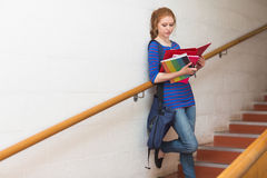 Redhead student reading notes on the stairs Royalty Free Stock Photo