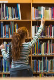 Redhead student taking book from shelf in library Royalty Free Stock Photo