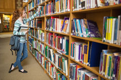 Redhead student taking book from shelf in the library Stock Image