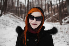 Redhead stylish girl with pale skin, blue eyes and burgundy, red lips with a shawl on her head. In a black coat on a background of a winter forest, smiling stock photos