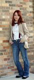 Redhead teen girl against brick wall Stock Images