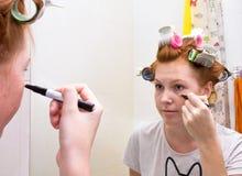Redhead teen girl doing makeup stock images