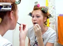 Redhead teen girl doing makeup stock photo