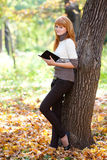 Redhead teenager woman reading a book Royalty Free Stock Photo
