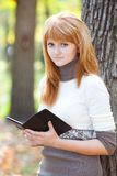 Redhead teenager woman reading a book Stock Photos