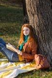 Redhead thoughtful attractive girl relaxing in autumn park Stock Photo