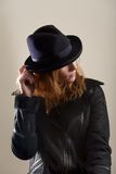 Redhead touching brim of blue felt hat stock photo