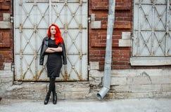 Redhead unformal κορίτσι που στέκεται κοντά στο τουβλότοιχο με τις πόρτες metall Αστικό ύφος οδών Στοκ εικόνες με δικαίωμα ελεύθερης χρήσης