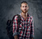 Redhead urban traveller male holds backpack. Stylish redhead urban traveller male holds backpack on grey background in a studio Royalty Free Stock Image