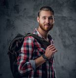 Redhead urban traveller male holds backpack. Stylish redhead urban traveller male holds backpack on grey background in a studio Stock Photo