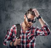 Redhead urban traveller male holds backpack. Stylish redhead urban traveller male in sunglasses holds backpack on grey background in a studio Royalty Free Stock Photography