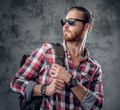 Redhead urban traveller male holds backpack. Stylish redhead urban traveller male in sunglasses holds backpack on grey background in a studio Stock Image