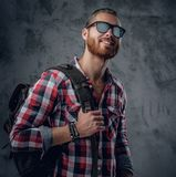 Redhead urban traveller male holds backpack. Stylish redhead urban traveller male in sunglasses holds backpack on grey background in a studio Royalty Free Stock Image