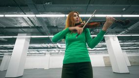 Redhead violinist is playing her instrument in a hall. 4K stock footage