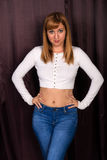 Redhead in white and blue. Pretty young redhead in a white knit blouse and jeans royalty free stock photography