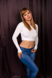 Redhead in white and blue. Pretty young redhead in a white knit blouse and jeans stock image