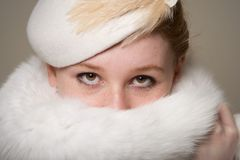 Redhead in white feathered hat with fur hiding mouth Royalty Free Stock Photos