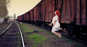 Redhead witch flying on the broom. On train station stock photos