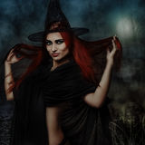 Redhead witch. Halloween fantasy theme: redhead witch girl in forest Stock Image