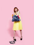 Redhead woman. Portrait of redhead woman desperatively searching for something in her bag stock photography