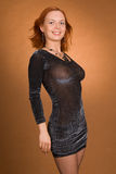 Redhead woman. Sexual translucent dress on the young redhead woman on brown background in a studio stock photography